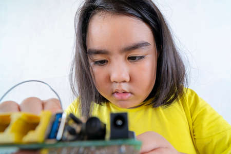 Asian women are learning simple electrical circuits. By learning from the laptop to find information about how to manually connect the circuit. Standard-Bild