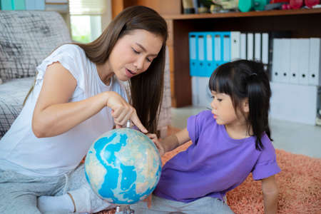 pretty family homeschooling mother happy teaching smart daughter private lessons in globe. Asia seriously girl children touch map and curious watching.