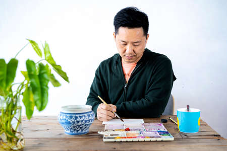 Asian male artist paints with a paint brush and watercolor palette on a laptop face paper. Standard-Bild