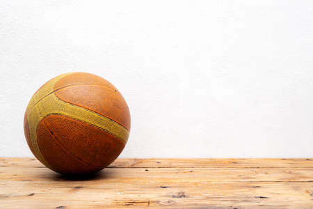 Basketball balls for sports and games are placed on a wooden table with white plaster walls.