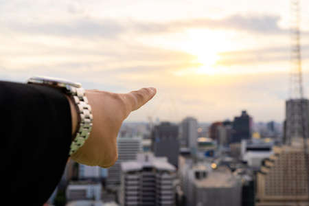 Business man pointing finger soft focus, Sunset city building background. Wear a beautiful suit, an elegant watch.