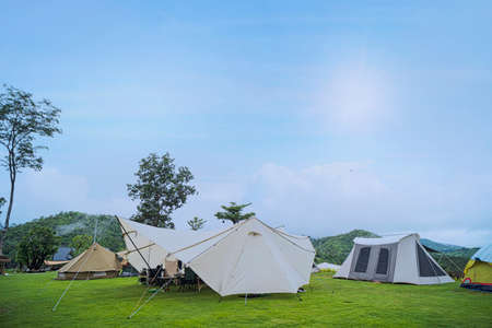 Camp and pitch a tent under the forest on the hill with a beautiful morning sun. Canvas cotton Bell tent in the yard decorated for summer kids party