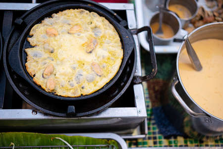 Fried mussel pancakes, Cooking mussel fried in egg batter on iron pan. Street food of Thailand.