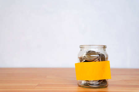 Glass jar with coins, with a label on the jar on a wooden table, white isolated background. Finance and investment concept. Standard-Bild