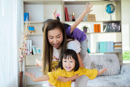 Happy family healthy cheerful young mum lifting cute little child daughter up playing plane doing gymnastic exercise in living room, funny kid girl flying in mothers arms look at camera having fun
