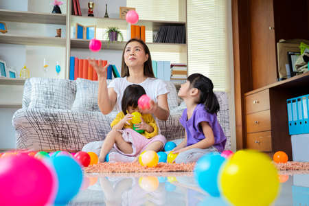 A mother, two Asian daughters, happily playing at home, mother and daughter smiles, they are with wind ball. Mom was throwing three balls in the air. Standard-Bild
