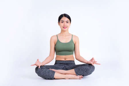 Sporty young woman doing yoga practice isolated on white background. Concept of healthy life and natural balance between body and mental development. Full length Standard-Bild