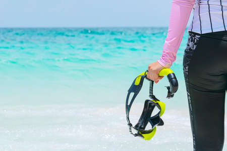 Women tourists holding diving equipment stands on a tropical beach ready to enter the water. Sea travel in Thailand concept