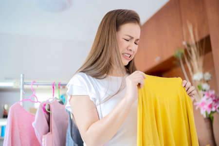 Woman smelling bad from her shirt because dirty laundry, smelly stinky musty from clothes