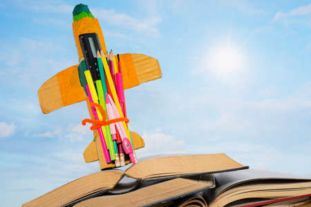 Education and back to school concept. cardboard rocket and pencils over books. The backdrop is a beautiful clear sky. 版權商用圖片