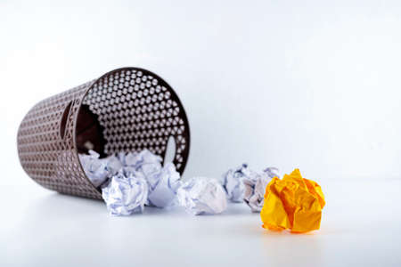 Crumpled paper in the trash can, white crumpled paper ball and different orange crumpled paper ball on a white background