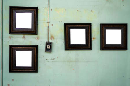 Four dark picture frames are hung in a gallery on an old wall. 版權商用圖片