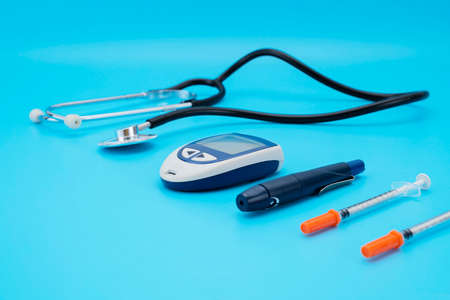 Apparatus for measuring the level of glucose in the blood, the test strip and a stethoscope on a blue background