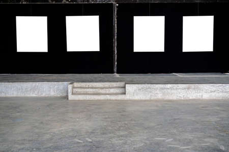 Four white picture frames were hung in a gallery on a black fabric wall. 版權商用圖片