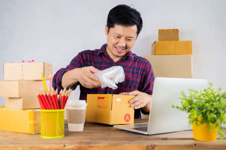 Happy young business owner packing materials and shockproof plastic into cardboard boxes. Man starts an online business. People with SME entrepreneurs online shopping or freelance work ideas. 版權商用圖片