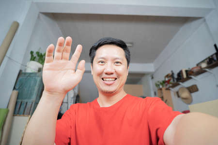 Happy blogger smiling face waving hand talking to webcam recording vlog, social media influencer streaming, making video call at home. Headshot portrait. Webcamera view