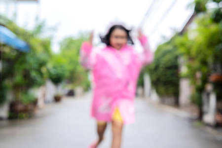 Blur background. Happy asian little child girl having fun to play with the rain in the evening
