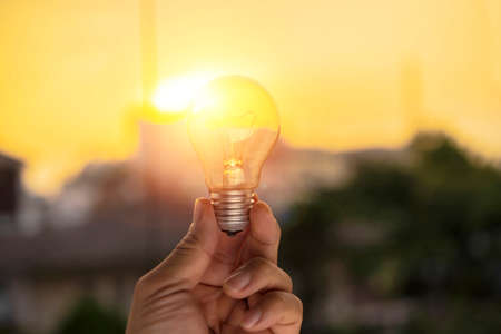 hand holding a light bulb with sunset power, sustainable development. Ecology concept 版權商用圖片