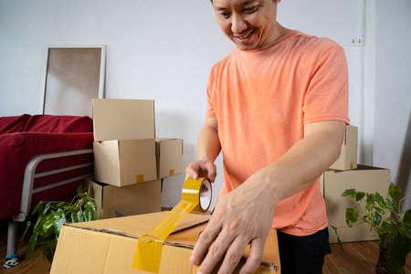 House moving concept. Closeup of man packing cardboard box, when preparing the cargo box, cargo box, natural shooting background 版權商用圖片
