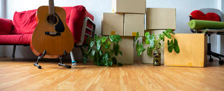 Horizontal photo heap of cardboard boxes with personal belongings in living room at moving relocation day no people, delivery service concept, banner for website header design with copy space for text 版權商用圖片