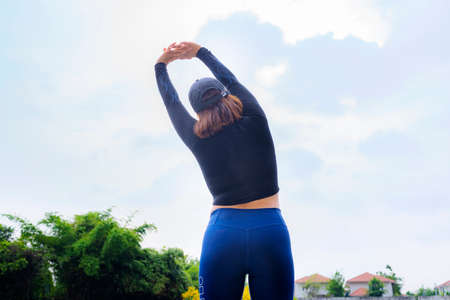 Young beautiful Asian woman in sports outfits doing stretching before workout outdoor in the park in the morning to get a healthy lifestyle. Healthy young woman warming up outdoors. 版權商用圖片