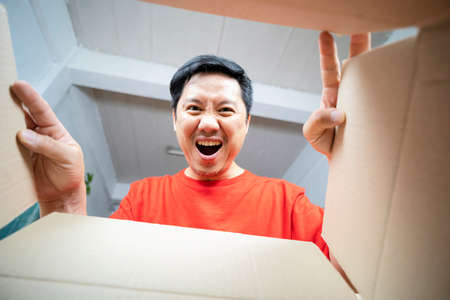 The surprised man unpacking, opening carton box and looking inside. The package, delivery, surprise, gift lifestyle concept. Human emotions and facial expressions concepts 版權商用圖片