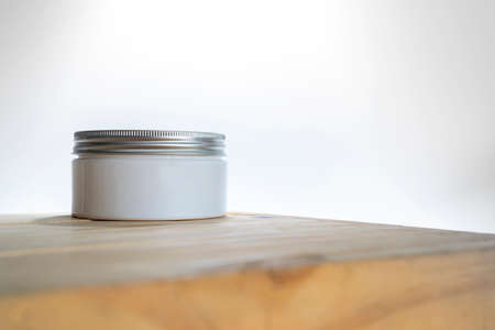 Jar with cream and board on white background, closeup