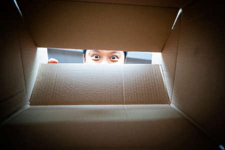 man peeking from a hole on cardboard box. Concept of a human trafficking, Spying and Curiosity 版權商用圖片