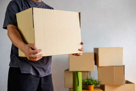 Midsection of man carrying open cardboard box in new home, cropped shot of man holding cardboard boxes while moving home