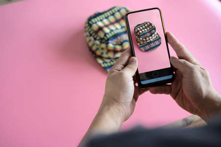 Men take photos of hats with their mobile phones or digital cameras on smartphones to post for sale online on the Internet.