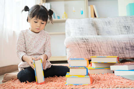 A little cute girl reading a picture book a book sitting on the floor 版權商用圖片