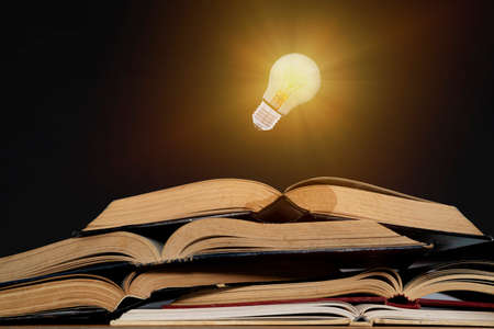 Light bulb and opened vintage book style vintage dark background,The idea of reading books, knowledge, and searching for new ideas,book bible.Concept