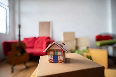 Model of the wooden house on the floor in the new bright sunny house. Moving boxes with belongings in empty room