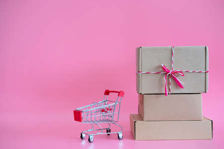 Paper boxes in a trolley with on pink background, Online shopping or ecommmerce concept 版權商用圖片