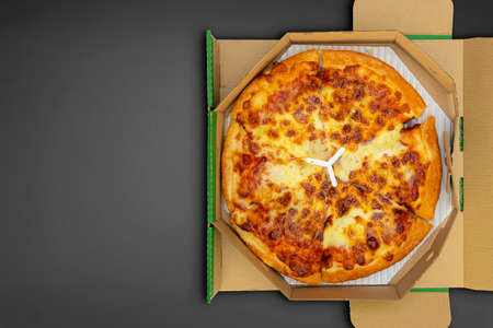 Pizza in a cardboard box on a black chalkboard background. Space for text. View from above. Pizza delivery. Pizza menu. 版權商用圖片