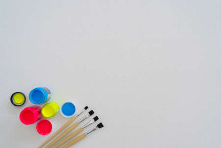 Paintbrushes and plastic paints are placed on a foam pad. Polystyrene foam texture and background. White foam sheet plastic.