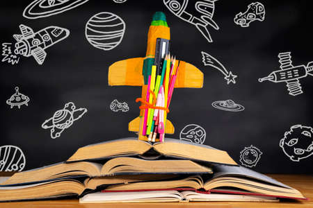 Education concept and back to school A cardboard rocket placed over a book in front of a blackboard depicting space objects in the classroom.