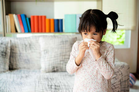 Runny nose. Sick little girl blowing her nose and covering it with handkerchief