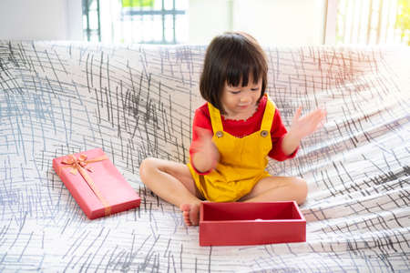 Present A surprised young Asian girl sits on a sofa opening a gift. Clapping my hands very much.