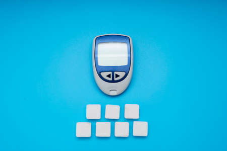 Sugar cubes and Glucose meter on blue background, world diabetes day. Copy space. Top view 版權商用圖片