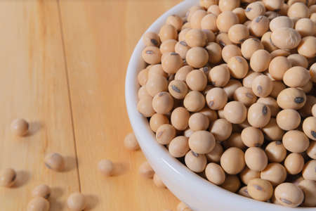 soybeans or soya beans in a bowl on white wooden background. top view. vegan food concept