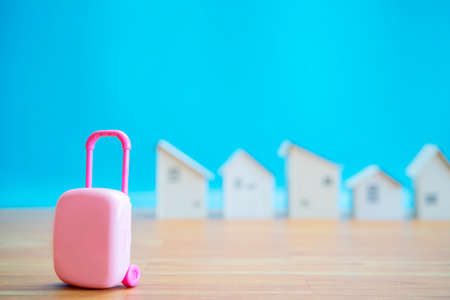 Small pink suitcase with tiny wooden house Holiday rentals ideas for renting homes and private rooms. 版權商用圖片