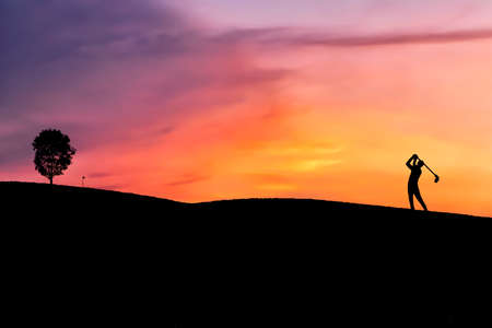 silhouette golfer hitting golf shot on sunset, in the summer for relax time. The flag that is intended