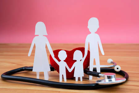 Take out health insurance for family. Stethoscope, heart of family on wooden background