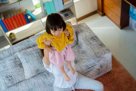 The mother held the child up high The child is very happy, the smile on the blooming face. Playing in the living room 版權商用圖片