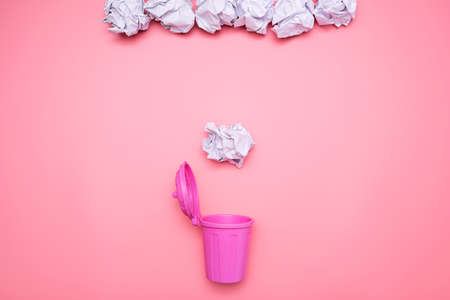 The crumpled paper is falling into the pink bin, lying on a pink background. 版權商用圖片