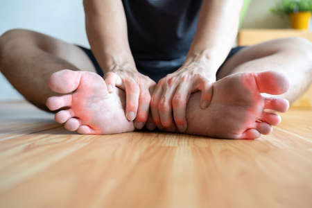 The man sitting in the room grabbing his feet after the gout flared, suffering from inflammation, swelling and pain.