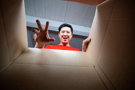 The surprised man unpacking, opening carton box and looking inside. The package, delivery, surprise, gift lifestyle concept. Human emotions and facial expressions concepts 版權商用圖片 - 168300225