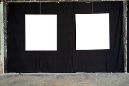 Two white picture frames were hung in a gallery on a black fabric wall.