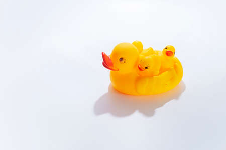 top view of family of yellow toy ducklings on white background, motherhood concept